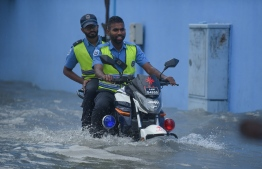 Traffic Police driving on a flooded street in Male' on November 5. PHOTO: AHMED NISHAATH/MIHAARU