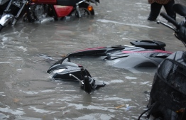 A motorcycle on its side on a flooded street in Male' on November 5. PHOTO: AHMED NISHAATH/MIHAARU