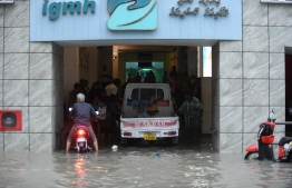 People seeking higher ground at Indhira Gandhi Memorial Hospital on a flooded street in Male' on November 5. PHOTO: AHMED NISHAATH/MIHAARU