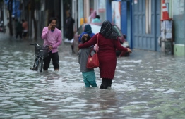 People walking on a flooded street in Male' on November 5. PHOTO: AHMED NISHAATH/MIHAARU