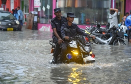 Police drive on a flooded street in Male' on November 5. PHOTO: AHMED NISHAATH/MIHAARU
