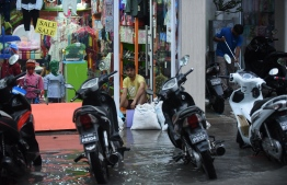 A man stacks sand bags to prevent flood water from entering a shop in Male City after heavy rains FILE PHOTO/MIHAARU