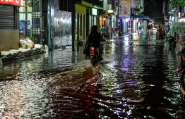 A motorcycle being driven on a flooded street in Male' on November 5. PHOTO: NISHAN ALI/MIHAARU