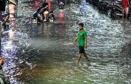 Man crosses a flooded street in Male' on November 5. PHOTO: NISHAN ALI/MIHAARU