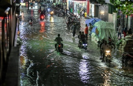 Motorcycles driving past on a flooded street in Male' on November 5. PHOTO: NISHAN