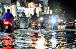 Motorcycles drive as WAMCO workers make their waste collection efforts during the heavy flooding of Male' on November 5. PHOTO: NISHAN ALI/MIHAARU