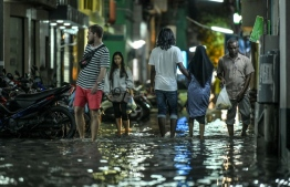 People walk on a flooded street in Male' on November 5. PHOTO: NISHAN ALI/MIHAARU