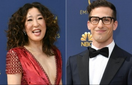 (COMBO) This combination of pictures created on December 05, 2018 shows actress Sandra Oh (L) and actor Andy Samberg (R) arriving for the 70th Emmy Awards at the Microsoft Theatre in Los Angeles, California on September 17, 2018. - The HFPA (Hollywood Foreign Press Association) has announced on December 5, 2018, actress Sandra Oh and actor Andy Samberg will be the 2019 Golden Globe ceremony hosts. (Photos by VALERIE MACON / AFP)