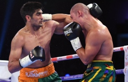 (FILES) In this file photo taken on August 5, 2017 Indian boxer and WBO Asia-Pacific Super Middleweight champion Vijender Singh (L) throws a punch at WBO Oriental Super Middleweight champion of China Zulpikar Maimaitiali during their double title bout at the National Sports Complex of India (NSCI) Dome in Mumbai. - Indian boxing superstar Vijender Singh is keen to trade punches with Mexico's Canelo Alvarez at Madison Square Garden after signing a new deal with the legendary US promoter Bob Arum. The 33-year-old Singh, a bronze medallist at the 2008 Beijing Olympics, has an unbeaten 10-0 record since he turned pro in 2015, but failed to get a single fight this year. (Photo by PUNIT PARANJPE / AFP)