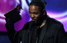 """(FILES) In this file photo taken on January 28, 2018 Kendrick Lamar receives the Grammy for the Best Rap Album with DAMN. during the 60th Annual Grammy Awards show in New York. - The soundtrack of Marvel's """"Black Panther"""" propelled rap superstar Kendrick Lamar to the front of 2018's Grammy pack with eight nominations, closely followed by fellow rapper Drake who scored seven. Women performers also achieved far greater presence in the 2019 edition of the top music awards, with Cardi B, Lady Gaga and folk-rock singer Brandi Carlile all nabbing nominations across the top categories. (Photo by Timothy A. CLARY / AFP)"""