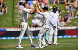 New Zealand's paceman Tim Southee (L) celebrates the dismissal of Sri Lanka's batsman Dinesh Chandimal with teammate Neil Wagner during day one of the first Test cricket match between New Zealand and Sri Lanka at the Basin Reserve in Wellington on December 15, 2018. (Photo by Marty MELVILLE / AFP)