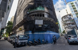 Pedestrians walk past a construction site in Male' City. PHOTO: AHMED NISHAATH / MIHAARU
