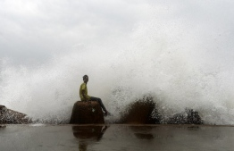 An Indian youth sits on a concrete block as waves hit a breakwater at Kasimedu fishing harbour as cyclone Phethai approaches the eastern Indian coast, in Chennai on December 16, 2018. - Cyclone Phethai is expected to make a landfall on December 17 with winds with a speed of 45-55 kmph, local media reported. (Photo by ARUN SANKAR / AFP)