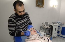 An Iraqi woman gets a facial treatment at a beauty clinic in the northern city of Mosul on November 19, 2018. - For three years, Mosul's women were covered in black from head to toe and its men had to keep their beards long. Salons were shut, and plastic surgery considered a crime. Today, Mosul's plastic surgeons and beauticians are at service. (Photo by Zaid AL-OBEIDI / AFP)