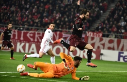Milan's Gonzalo Higuain (R) avoids the tackled of Olympiacos goalkeeper Jose Sa during the UEFA Europa league football match between Olympiakos Piraeus and AC Milan at the Karaiskaki stadium in Piraeus on December 13, 2018. (Photo by ARIS MESSINIS / AFP)
