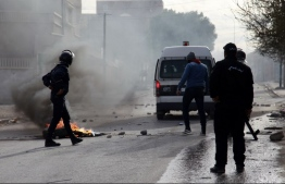 Tunisian policemen stand in a street during a demonstration on December 25, 2018 in the central Tunisian city of Kasserine. - A Tunisian journalist has died after setting himself on fire, officials said, in a protest over harsh living conditions that prompted overnight clashes with police in the country's west. Police fired tear gas at dozens of people who took to the streets Monday night in the city of Kasserine, 270 kilometres (165 miles) from the capital, setting tyres ablaze and blocking the main street. (Photo by Hatem SALHI / AFP)