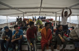 (FILES) In this file photo taken on July 2, 2018 migrants wait on the deck of the NGO Proactiva Open Arms boat after being rescued as they tried to cross the Mediterranean from Libya. - The number of migrants who died attempting to cross the Mediterranean fell by more than a quarter in 2018 over the previous year, with 2,262 people reported dead or missing, the UN refugee agency said on January 3, 2019. The number of migrants who arrived in Europe after surviving the sea crossing also dropped by roughly the same amount last year to 113,482  after 172,301 in 2017, according to the agency's full-year figures. (Photo by Olmo Calvo / AFP)