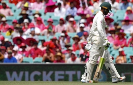Australia's Usman Khawaja walks off the ground after being dismissed during the third day's play of the fourth and final cricket Test between India and Australia at the Sydney Cricket Ground on January 5, 2019. (Photo by DAVID GRAY / AFP) /