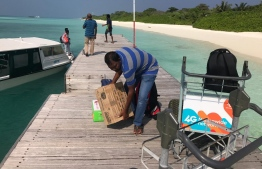 Travellers load luggage on a trolley at the jetty of HDh.Hanimaadhoo. PHOTO/MIHAARU