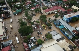 This general view shows a flooded area in the town of Baao in Camarines Sur province on December 30, 2018. - Four people were killed in landslides and thousands of others evacuated from their homes after a storm swept through the central Philippine islands on December 29, officials said. (Photo by Simvale SAYAT / AFP)
