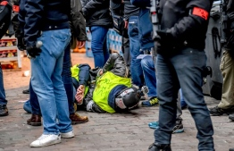 """Yellow vest"" (gilets jaunes) protestors lay on the ground after being arrested by French police on the sideline of an anti-government demonstration in Lille, northern France, on January 5, 2019. - The ""yellow vest"" movement began in rural France over fuel taxes and quickly ballooned into a wider revolt against the 41-year-old president's pro-business policies and perceived arrogance by low-paid workers and pensioners. (Photo by Philippe HUGUEN / AFP)"