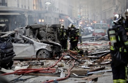 Firefighters intervene in the middle of debris after the explosion of a bakery on the corner of the streets Saint-Cecile and Rue de Trevise in central Paris on January 12, 2019. - A large explosion badly damaged a bakery in central Paris on January 12, injuring several people and smashing windows in surrounding buildings, police and AFP journalists at the scene said. A fire broke out after the blast at around 9am (0800 GMT) in the busy 9th district of the city, which police suspect may have been caused by a gas leak. (Photo by Thomas SAMSON / AFP)