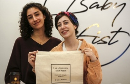"Palestinian fashion designer and label founder Yasmeen Mjalli (L), along with her creative director Amira Khader, pose for a picture with one of their label ""BabyFist's"" canvas bags in their shop in Ramallah in the occupied West Bank on December 19, 2018. - It's only three words on a T-shirt or embroidered on a denim jacket, but they carry a powerful message: ""Not you habibti (darling)."" ""BabyFist"" label founder Yasmeen Mjalli, 22, sees the clothes helping to empower Palestinian women facing unwelcome male attention in public, placing on the fabrics of muted colours and on canvas bags messages in English and Arabic inside drawings of flowers and other designs. (Photo by ABBAS MOMANI / AFP)"