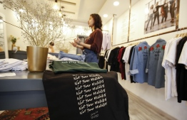 "Palestinian fashion designer Yasmeen Mjalli speaks while standing in her clothing shop where her label collection ""BabyFist"" carrying anti-sexual harassment slogans is showcased, in Ramallah in the occupied West Bank on December 19, 2018. - It's only three words on a T-shirt or embroidered on a denim jacket, but they carry a powerful message: ""Not you habibti (darling)."" ""BabyFist"" label founder Yasmeen Mjalli, 22, sees the clothes helping to empower Palestinian women facing unwelcome male attention in public, placing on the fabrics of muted colours and on canvas bags messages in English and Arabic inside drawings of flowers and other designs. (Photo by ABBAS MOMANI / AFP)"