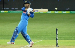 (FILES) In this file photo taken on January 15, 2019 Indian batsman Mahendra Singh Dhoni hits the ball during the second one-day international cricket match between Australia and India at the Adelaide Oval. - Mahendra Singh Dhoni on January 16 got plaudits for his match-winning fifty in India's series-levelling win over Australia as he answered his critics with a 'classic' finishing job. (Photo by Brenton EDWARDS / AFP) /
