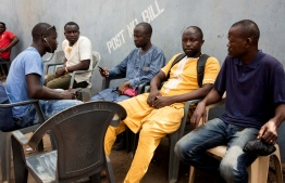 Mansuru Tahiru (2nd R) the cousin of murdered Ghanian undercover reporter Ahmed Hussein Suale sits with friends during a mourning gathering in Accra on January 17, 2019. - Family and friends gather to discuss the murder of Ghanian undercover reporter Ahmed Hussein Suale at a popular spot where he used to sit and drink with family and friends in Accra. Ghanaian police on January 17, 2019 opened an investigation after an undercover journalist who helped expose corruption in African football was shot dead. (Photo by RUTH MCDOWALL / AFP)