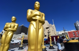 (FILES) In this file photo taken on February 24, 2016 Rick Roberts works on touching up a base amid statues of the Oscar awaiting finishing up at a Hollywood back lot in Hollywood, California ahead this weekend's 88th Academy Awards. - Hollywood's biggest night -- the Oscars -- is set to take place in Febuary 2019 without a host for the first time in 30 years, after comedian Kevin Hart pulled out of the gig and no suitable replacement was found. Though organizers have yet to confirm the plans, entertainment insiders say the show's producers are forging ahead with preparations for the 91st Academy Awards on February 24 with no emcee. (Photo by FREDERIC J. BROWN / AFP)
