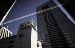 Toshiba Corp. signage displayed atop the company's headquarters is seen through a train window in Tokyo, Japan, on Monday, Jan. 23, 2017. Toshiba's shares climbed the most in three weeks on Monday after reports that the company's plan to sell a stake in its chip unit is drawing attention from possible investors. Photographer: Kiyoshi Ota/Bloomberg
