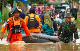 Indonesian rescuers evacuate residents from their homes in Makassar on January 24, 2019 as heavy rain and strong winds pounded the southern part of Sulawesi island, swelling rivers that burst their banks and inundating dozens of communities in nine southern districts. - The death toll from flash floods and landslides in Indonesia jumped to 26, a disaster agency official said on January 24, as rescuers race to find still-missing victims. (Photo by YUSUF WAHIL / AFP)