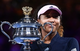 Japan's Naomi Osaka celebrates with the championship trophy during the presentation ceremony after her victory against Czech Republic's Petra Kvitova in the women's singles final on day 13 of the Australian Open tennis tournament in Melbourne on January 26, 2019. (Photo by Jewel SAMAD / AFP)