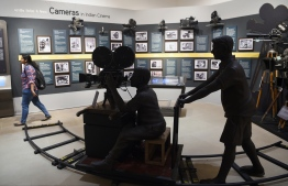 In this picture taken on January 22, 2019, an Indian student (R) visits the National Museum of Indian Cinema (NMIC), the country's first museum showcasing the history of its film industry, in Mumbai. - From silent black-and-white films to colourful blockbusters bursting with song and dance, a new museum tracing the evolution of Indian cinema has opened in the home of Bollywood. Costing 1.4 billion rupees (19.6 million USD), India's first national film museum is spread across a stylish 19th-century bungalow and a modern five-storey glass structure in south Mumbai. (Photo by PUNIT PARANJPE / AFP) /