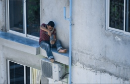 An expatriate worker operates on a small balcony of an apartment building without the use of safety equipment. PHOTO: HUSSAIN WAHEED / MIHAARU
