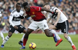 Manchester United's French midfielder Paul Pogba (C) vies with Fulham's English defender Calum Chambers (R) and Fulham's Ivorian midfielder Jean Michael Seri (L) during the English Premier League football match between Fulham and Manchester United at Craven Cottage in London on February 9, 2019. - Manchester United won the game 3-0. (Photo by Ian KINGTON / AFP) / RESTRICTED TO EDITORIAL USE. No use with unauthorized audio, video, data, fixture lists, club/league logos or 'live' services. Online in-match use limited to 120 images. An additional 40 images may be used in extra time. No video emulation. Social media in-match use limited to 120 images. An additional 40 images may be used in extra time. No use in betting publications, games or single club/league/player publications. /