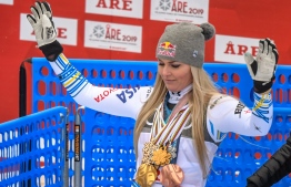 US' Lindsey Vonn walks in the mixed zone with all the medals she earned during her career after the Women's Downhill event of the 2019 FIS Alpine Ski World Championships at the National Arena in Are, Sweden on February 10, 2019. - Vonn, 34, who will retire from competitive skiing, is the most successful women skier of all time, with a record 20 World Cup titles to her name and 82 victories on the circuit. (Photo by FRANCOIS XAVIER MARIT / AFP)