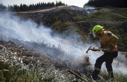 This handout picture taken on February 8, 2019 and received on February 11 from the New Zealand Defence Force shows a firefighter combating a bushfire near Nelson in New Zealand's South Island. - A large New Zealand wildfire is set to keep burning until next month but has moved away from danger areas and residents of an evacuated village should be able to return home soon, firefighters said on February 11. (Photo by Chad SHARMAN / NEW ZEALAND DEFENCE FORCE / AFP) /