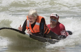 Pamela Hanford, 75, is helped by a team of coaches and volunteers to surf at an adaptive surfing event at Muizenberg beach, on January 20, 2019, in Cape Town, South Africa. - Hansford broke her neck while bodyboarding, but was determined to get back into the sea, even though she can't walk. Adaptive surfing is an initiative aimed at giving disabled people access to the ocean, and to surfing in particular. This is made possible by having a team of coaches and helpers to get the surfers in and out of the water, safely. (Photo by RODGER BOSCH / AFP)