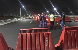 Police officers conducting a security check on a motorcycle travelling along the Sinamale' Bridge. PHOTO: MALDIVES POLICE SERVICE