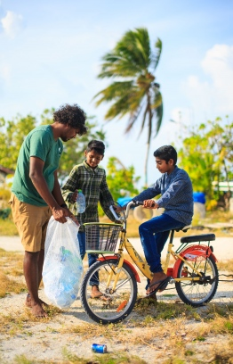 Shameel from Stand Up For Our Seas team cleans up Thuladhoo with local little ones. PHOTO: JAMES APPLETON PHOTOGRAPHY / STAND UP FOR OUR SEAS.