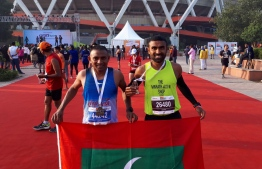 Mohamed Rasheed and Nasru posing with the Maldivian flag after the race. PHOTO: MIHAARU