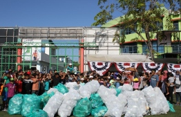 Participants posing for a picture with the waste collected. PHOTO: AMERICAN CENTER
