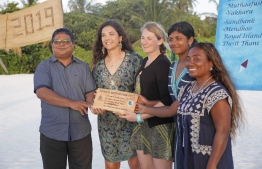 Environment Minister Dr. Hussain Rasheed Hassan presents (from left to right) Dr. Claire Petros, Dr. Cal Major, Dhafeena Hassan and Shaziya Saeed with a wooden plaque from Coco Collection and Olive Ridley Project, in recognition of their achievement. PHOTO: JAMES APPLETON PHOTOGRAPHY