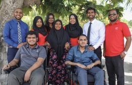 Bank of Maldives staff posing for a picture with recipients of the Motorised Wheelchair Donation programme. PHOTO: BANK OF MALDIVES