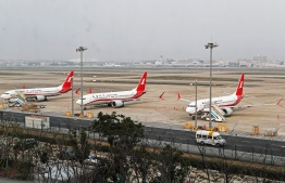 This photo taken on March 11, 2019 shows three Boeing 737 MAX 8 planes from Shanghai Airlines parked at Shanghai Hongqiao International Airport in Shanghai. - China on March 11, 2019 ordered domestic airlines to suspend commercial operation of the Boeing 737 MAX 8, citing the Ethiopian Airlines crash and another deadly accident of that same model in Indonesia. (Photo by STR / AFP)