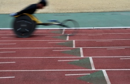 """This photo taken on February 13, 2019 shows Japanese Paralympian Masayuki Higuchi during a training session at a track and field stadium in Noda, Chiba prefecture. - For Higuchi, a middle-distance athlete who competed at the 2016 Rio Paralympics, the most important aspect of the wheelchair is """"stability at high speed."""" (Photo by Toshifumi KITAMURA / AFP) /"""