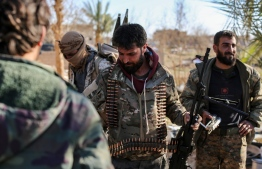 Fighters with the Syrian Democratic Forces (SDF) stand at a makeshift camp for Islamic State (IS) group members and their families in the town of Baghouz, in the eastern Syrian province of Deir Ezzor, on March 9, 2019. - Pushed flush along a bend in the Euphrates River, the scrap of a desert hamlet that is Baghouz in eastern Syria is the only territory IS jihadists have left. (Photo by Dylan COLLINS / AFP)