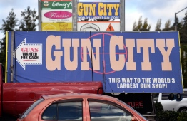 Signs point towards a gun shop in Christchurch March 21, 2019, claiming to be the world's largest gun shop. - New Zealand imposed an immediate ban on assault weapons on Thursday, taking swift action in response to the Christchurch massacre and triggering renewed calls from leading American politicians for curbs in the United States. (Photo by WILLIAM WEST / AFP)